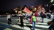 People who are against the Tokyo 2020 Olympics set to open in July, march around Tokyo's National Stadium, back, during an anti…