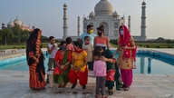 A group of Indians who visited the Taj Mahal monument that was Wednesday reopened to public after the lockdown to curb the spread of coronavirus gather to get photographed in Agra, India, June 16, 2021.