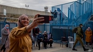 FILE - In this Feb. 23, 2021, file photo, Palestinians take a selfie after receiving the coronavirus vaccine from an Israeli…