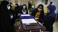 Election officials open a ballot box for the presidential elections at a polling station in Tehran, Iran, early Saturday, June…