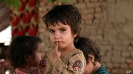An Afghan refugee girl looks at a photographer while playing with her friends at a Khazana refugee camp on the outskirts of…