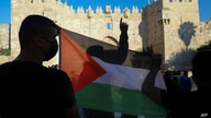 FILE - Palestinians demonstrators wave the Palestinian flag during protest in Damascus gate.