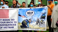 FILE - In this Friday, April 30, 2021, file photo former Afghan interpreters hold banners during a protest against the U.S…