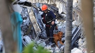 Fire rescue personnel conduct a search and rescue with dogs through the rubble of the Champlain Towers South Condo after the…