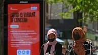 """FILE - Pedestrians walk past a sign warning members of the public about a """"Coronavirus variant of concern,"""" in Hounslow, west London, Britain, June 1, 2021."""