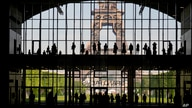 """Visitors gather during a presentation visit of the """"Grand Palais Ephemere"""", with the Eiffel Tower seeing outside, in Paris, France."""
