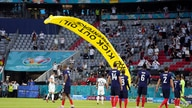 A Greenpeace paraglider lands on the pitch before the Euro 2020 soccer championship group F match between France and Germany at the Allianz Arena in Munich, Germany, June 15, 2021.