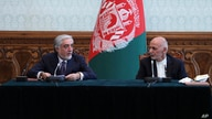 FILE - Afghan President Ashraf Ghani, right, and his then-political rival Abdullah Abdullah speak after signing a power-sharing agreement at the presidential palace in Kabul, Afghanistan, May 17, 2020.