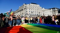 FILE - People gather at a giant rainbow flag during a rally in front of the Hungarian Parliament in Budapest, Hungary, June. 14, 2021, calling on lawmakers to reject legislation banning any content portraying homosexuality or sex reassignment to minors.