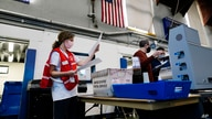 FILE - Election workers process mail-in and absentee ballots to scan for the 2020 U.S. general election at West Chester University, in West Chester, Pennsylvania, Nov. 4, 2020.