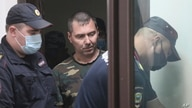 Alexander Popov, arrested on suspicion of murdering American student Catherine Serou, is escorted by police officers into a courtroom in the city of Gorodets, north-west of Nizhny Novgorod, Russia, June 20, 2021.