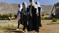 Afghan girl students cover their faces with scarfs as they walk inside the compound of their school after it was reopened,…