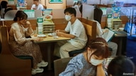 People sit in a restaurant using plexiglass separators to protect customers from coronavirus (COVID-19) disease in the Shibuya area of Tokyo, Japan, July 29, 2021.