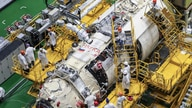 """FILE - A handout photograph released by the Russian Space Agency Roscosmos July 21, 2021, shows workers preparing the module """"Nauka"""" (Science) at the Baikonur cosmodrome in Kazakhstan. The module docked at the International Space Station Thursday."""