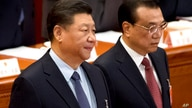 Chinese President Xi Jinping, left, stands as Premier Li Keqiang arrives for the closing session of China's National People's…