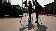 FILE - Afghan journalists film at the site of a bombing attack in Kabul, Afghanistan, Feb. 9, 2021.