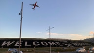 A giant sign painted near the main runway of the Wellington International Airport greets travelers returning home in Wellington…