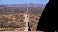 FILE - In this May 19, 2021 file photo the border wall stretches along the landscape near Sasabe, Ariz. The bodies of an…