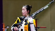 Yang Qian, of China, reacts after winning the gold medal in the women's 10-meter air rifle at the Asaka Shooting Range in the…