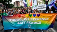 """People march holding a banner that reads """"Do you know who you love? Whoever you want!"""" march during a gay pride parade in…"""