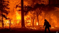 A firefighter passes a burning home as the Dixie Fire flares in Plumas County, Calif., Saturday, July 24, 2021. The fire…