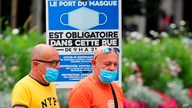 People wearing face masks to protect against coronavirus walk past a sign stating face coverings are required in the street, in…