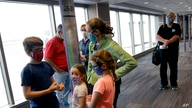 FILE - People wearing masks wait to board a Southwest Airlines flight at Kansas City International airport in Kansas City, Mo.,…