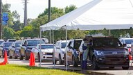 Cars line up at Miami Dade College North campus' COVID-19 testing site, Thursday, July 29, 2021, in Miami. Hospital admissions…