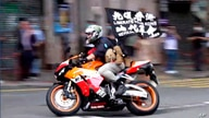 """FILE - In this Wednesday, July 1, 2020, file image made from video, motorcyclist Tong Ying-kit carries a flag reading """"Liberate…"""