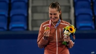 Belinda Bencic, of Switzerland, looks at her gold medal in the women's singles of the tennis competition at the 2020 Summer…