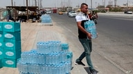 FILE - A man buys drinking water in Basra, southeast of Baghdad, Iraq, July, 21, 2019.