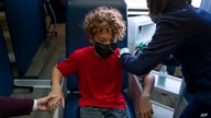 FILE - Max Cuevas, 12, receives the Pfizer COVID-19 vaccine at Families Together of Orange County in Tustin, California, May 13, 2021.