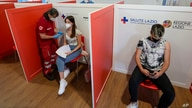 FILE - A young woman is administered her first dose of a COVID-19 vaccine, at a vaccination site set up in a shopping mall on the outskirts of Rome, Italy, June 1, 2021.
