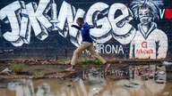 FILE - A boy leaps across a flooded area next to an informational mural with words in Swahili advising people to protect themselves from the coronavirus and get vaccinated, in the low-income Kibera neighborhood of Nairobi, Kenya, June 12, 2021.