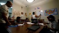 Arlena Brown, center, holds her youngest child, Lucy, 9 months, as she and husband, Robert, left, lead their other children through math practice at their home in Austin, Texas, July 13, 2021.
