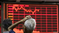 FILE - An investor looks at an electronic board showing stock information at a brokerage house in Beijing, China, Aug. 27, 2015.