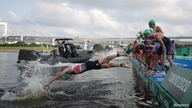 An athlete dives in on a false start in the men's Olympic triathlon at Odaiba Marine Park, Tokyo, Japan, July 26, 2021.