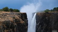 FILE - Visitors walk along a walkway as spray rises up from a flowing section of Victoria Falls, Zimbabwe, Dec. 4, 2019.