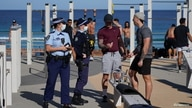 Patrolling police officers check IDs of people working out at a Bondi Beach outdoor gym area during a lockdown to curb the spread of COVID-19 outbreak in Sydney, Australia, July 27, 2021.