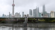 A man with luggage walks in the rain on The Bund as Typhoon In-fa approaches Shanghai, China, July 25, 2021.