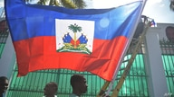 Workers place flags on a wall at the National Palace in the Haitian capital Port-au-Prince, on February 6, 2017 one day before…