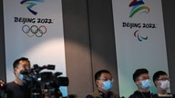 Reporters are seen in front of the Beijing 2022 Winter Olympic and Paralympic Games signs during a news conference on the…