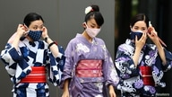 Women in traditional costumes, wearing protective face masks, walk outside the National Stadium, the main venue of the Tokyo…