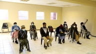 FILE - People wearing protective masks sit ahead of a vaccination, as South Africa rolls out the coronavirus disease (COVID-19) vaccines to the elderly at the Munsieville Care for the Aged Centre outside Johannesburg, South Africa, May 17, 2021.