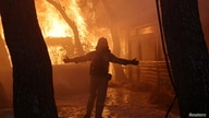 FILE PHOTO: A firefighter reacts as a wildfire burns at Varympompi suburb north of Athens, Greece, August 3, 2021. REUTERS…