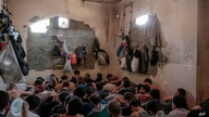 FILE - In this Tuesday, July 18, 2017 file photo, Suspected Islamic State members sit inside a small room in a prison south of…