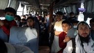 Afghans sit inside a bus that is leaving for Iran, in Kabul, Afghanistan, Wednesday, June 30, 2021. Frustration and anxiety…