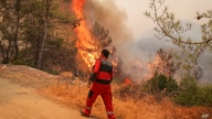 Firefighters work in the smoke-engulfed Mazi area as wildfires rolled down the hill toward the seashore, forcing people to be…