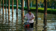 In this July 26, 2021, file photo, a man pushes a scooter through floodwaters in Xinxiang in central China's Henan Province,…