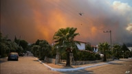 A helicopter flies as a fire engulfs the area in Oren, near Bodrum, Turkey, Aug. 3, 2021.